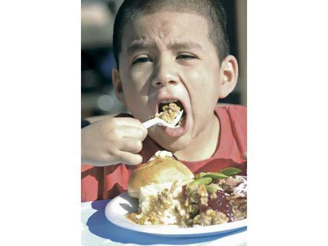 Hector Guzma, 4, of Newhall, takes a bite of stuffing at the Thanksgiving feast at Newhall Bicycle Company Thursday.