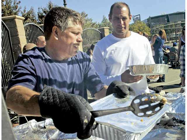 Volunteers Steve Lindahl, left, and George Corona warm up another pan of mashed potatoes as they help serve an estimated 450 free turkey dinners at the Newhall Bicycle Company's Thanksgiving feast in Newhall on Saturday.