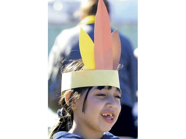 Bessy Hernandez, 4, of Newhall, wears a turkey-feather hat at the Thanksgiving feast presented free  to all who attended the event hosted by Newhall Bicycle Company in Newhall on Saturday.