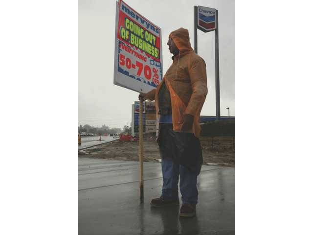 Alfonso Cruz, from Canyon Country, stands in the rain as he holds a sign on the corner of Magic Mountain Parkway and The Old Road Wednesday afternoon.