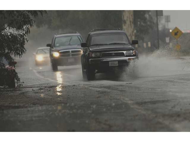 Motorists head east on Henry Mayo Drive on a wet Wednesday afternoon. Rain was forecast to continue through today.