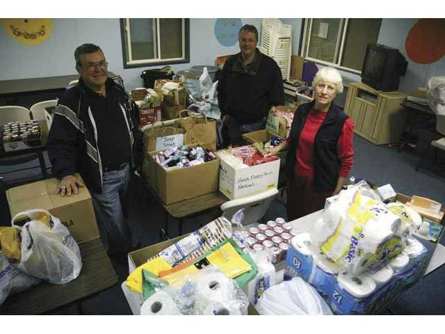 Tim Davis (left) and Andy Pattantyus of the Santa Clarita Community Development Corp. and volunteer Melanie Dvorak process food and other items donated to the Santa Clarita Emergency Winter Shelter, which opens Monday.