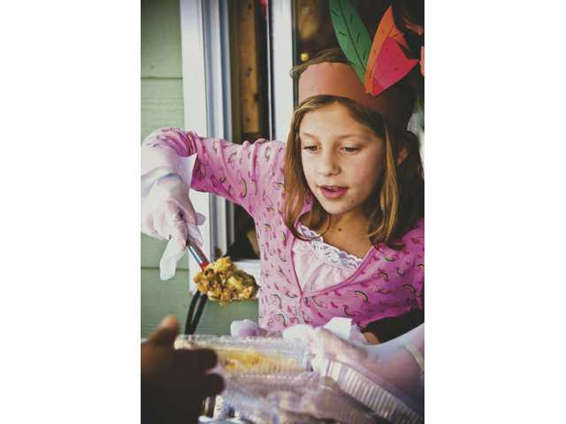 Kacie Nielson, 8, from Newhall passes out stuffing during the annual Thanksgiving Day dinner held at the Newhall Bicycle shop on Railroad Avenue.