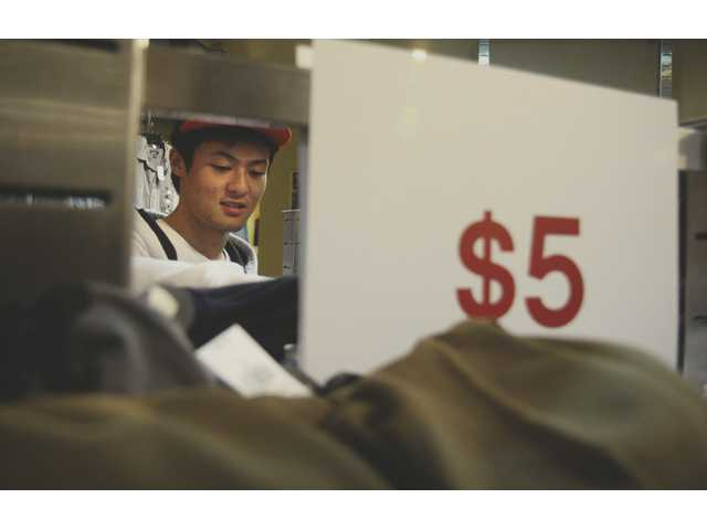 Allan Gao, 18, peruses sale racks at Anchor Blue in Town Center.
