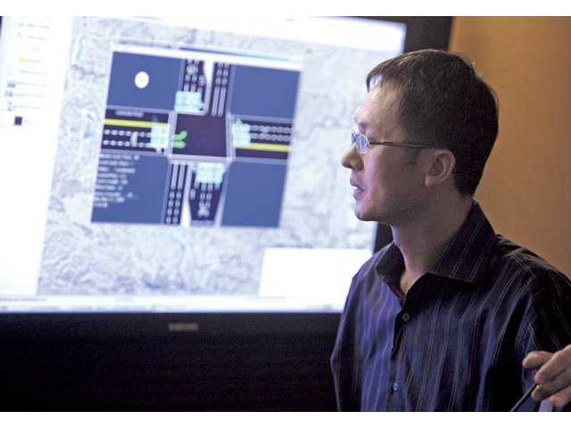 City Traffic Engineer Andrew Yi looks at a map on a 46-inch screen that shows traffic patterns in various locations around the city of Santa Clarita on Monday in the Traffic Control room inside City Hall.