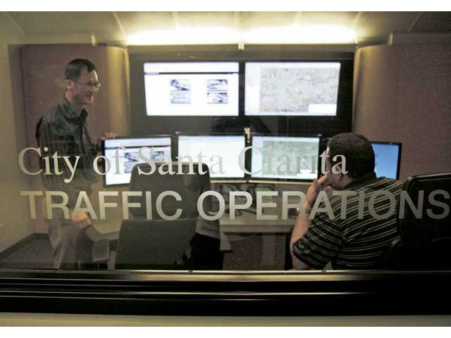 City Traffic Engineer Andrew Yi, left, and Cesar Romo, Signal Operations Supervisor inside the traffic control room at City Hall on Monday. They can detect problems at about 170 intersections in Santa Clarita via cameras.