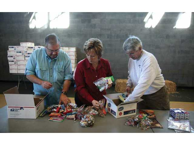 Left to right: Pete and Debbie Mahoney and Joe Avignone assemble care packages Saturday at the Santa Clarita Community Center. Local residents helped pack 450 boxes, which will be shipped out this week to American servicemen and women deployed around the world.