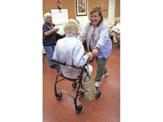 Angelica Gambirazio, a certified nursing assistant, helps wheel Anne Anthony around the Adult Day Care Center on Tuesday.