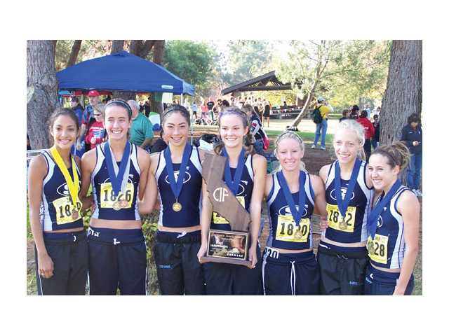 (From left to right) Brianna Jauregui, Amber Murakami, Stephanie Bulder, Anne Randall, Keri Molt, Karis Frankian, and Kaylin Mahoney show off the CIF State Division II Cross Country Championship trophy after a dominating victory in Fresno, their third straight state title. Mahoney took individual title with a first-place time of 17:34.