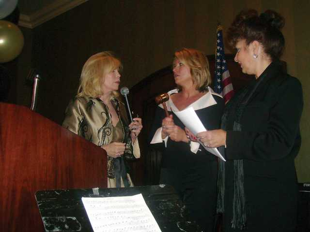 Outgoing president Doreen Chastain-Shine, left, and the mistress of ceremonies, Laura Langen, middle, of LandAmerica Southland Title, welcome Nancy Starczyk, right, to the stage for her Incoming President's Address. Starczyk serves as president of the Southland Regional Association of Realtors Inc. Santa Clarity Valley division for the third time.