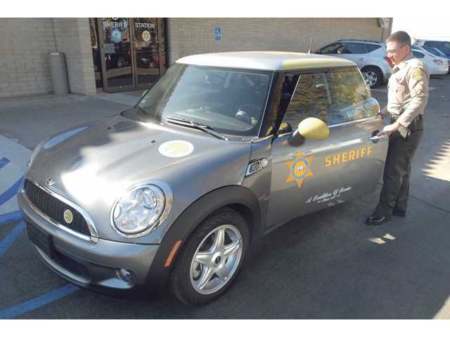 Santa Clarita Valley Sheriff's Sgt. Ron Shaffer demonstrates the all-electric MINI Cooper test vehicle at the SCV Sheriff's Station last week.