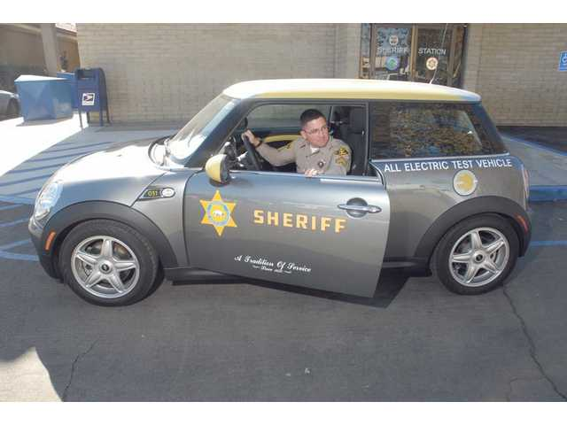 Santa Clarita Valley Sheriff's Sgt. Ron Shaffer demonstrates the all-electric MINI E test vehicle at the SCV Sheriff's Station on Wednesday. MINI Cooper is leasing 17 electric cars to about 12 Los Angeles County sheriff's stations in order to help cut back on harmful emissions.