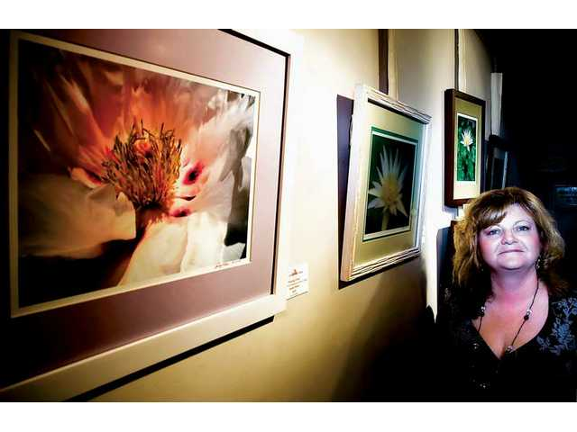 "Photographer Sandy Fisher, a two-time cancer survivor, stands next her photos titled ""Blushing Peony"" and ""Peace Like a Flower,"" which are on display at the Canyon Theatre Guild in downtown Newhall."