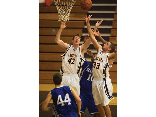 COC's Brooks Flanagan (42) and teammate Behrang Behjoo (33) rebound over their opponents from El Camino in Tuesday night's 72-70 Cougar victory.