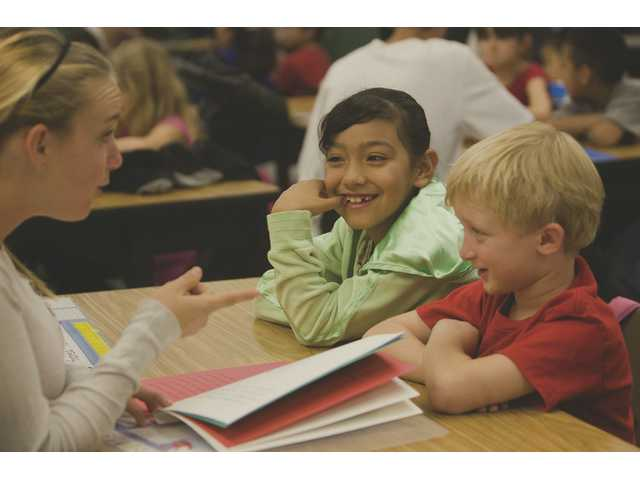 "Andrea Juarez and Nathan Bunkell, second-graders at Old Orchard Elementary School, react as a Placerita Junior High School eighth-grader reads them ""A Trip to Candy World."""