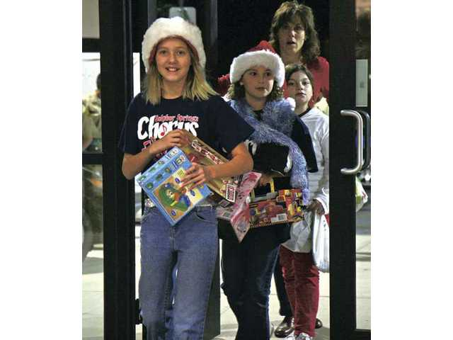 Sulphur Springs Elementary School students Sally Hyde, foreground, and Katy Clow walk into the Power Honda Valencia car dealership to drop off toys during the kickoff to the SCV Sheriff's Station's annual toy drive on Thursday.