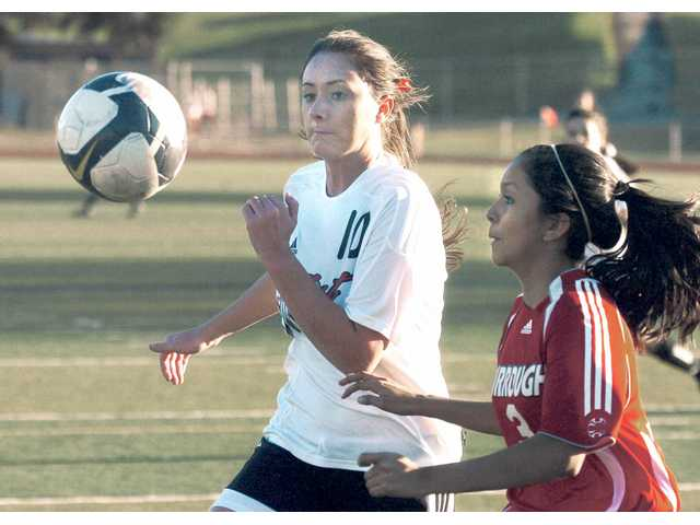Hart's Brittany Ballew (10) chases the ball with Burroughs' Ashley Caro on Thursday at Hart High.