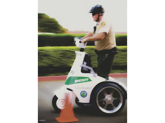 Deputy Jeremy Conn speeds past a cone on a high-speed slalom test track during the T-3 electric vehicle training held behind the SCV Sheriff's Station.