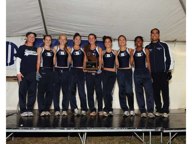 The Saugus girls cross country team shows off the CIF State Division II cross country championship they won in Fresno last Saturday.