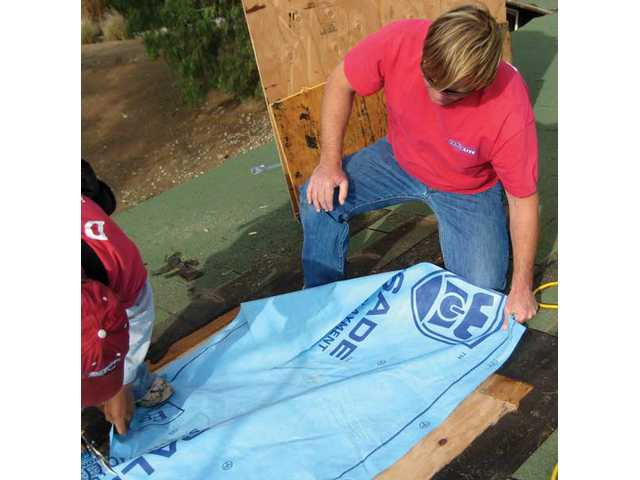 Daniel Jones uses a blue synthetic material to replace the old asphalt paper above the plywood and below the asphalt shingles. The new material is more flexible than asphalt paper and won't crack when an older house moves and shifts.