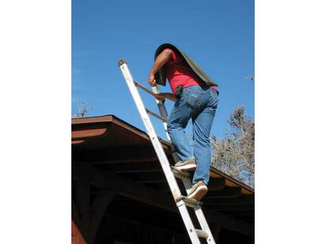 Daniel Jones of Daniel Roofing & Construction inspects and replaces shingles on the roof of a Mint Canyon home.