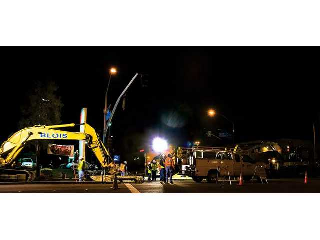 Night construction crews work on the corner of Valencia and Creekside on Thursday.
