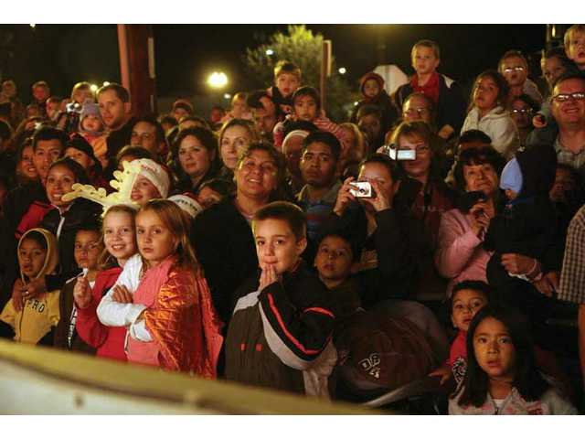 A crowd of Santa Clarita locals watches as Santa and friends pull into the Newhall Metrolink station aboard the Holiday Toy Express Friday night.