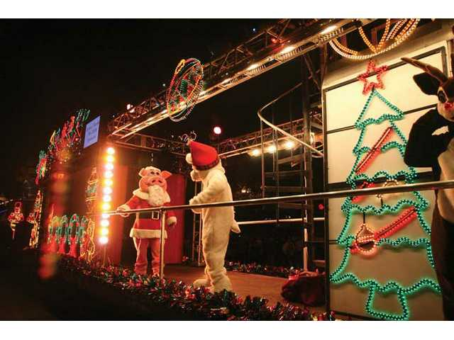 Performers aboard the Holiday Toy Express Metrolink train sing and dance for the crowd at the Newhall Metrolink station Friday night.