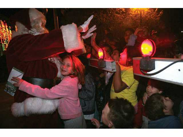 Kids hug and high-five Santa as he makes his way around the crowd after the Holiday Toy Express pulled into the Metrolink station in Newhall Friday night.