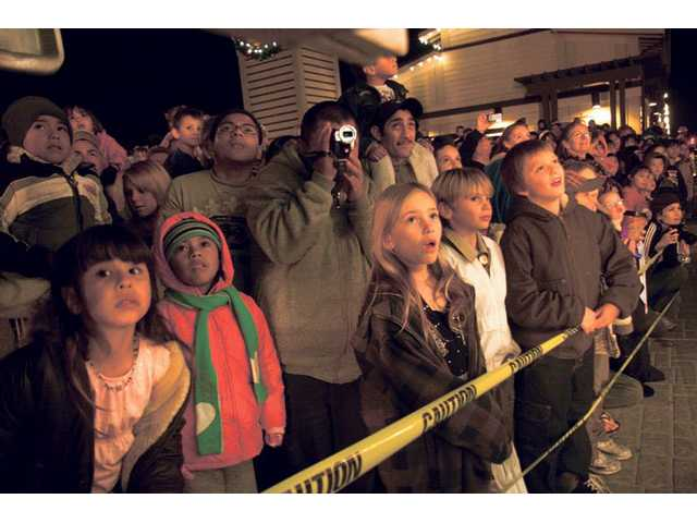 Children and their parents watch the Metrolink Holiday Toy Express train as it rolls into the Newhall Metrolink Station on Friday night. The 13-year tradition helps Santa and Mrs. Claus make 47 visits over a 5-week period leading up to Christmas.