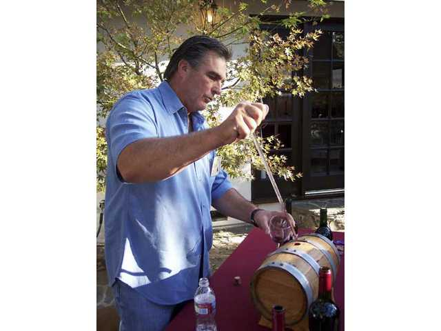 "Chris Carpenter provides guests a barrel sample of his Compa Vineyard wine at ""Sunset in the Vineyard"" at his Newhall home."