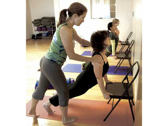 Instructor Kim Henigman, left, works with Isabel Shinkarik, of Valencia, during a beginning Yoga class at Yoga Yoga in Newhall on Friday.