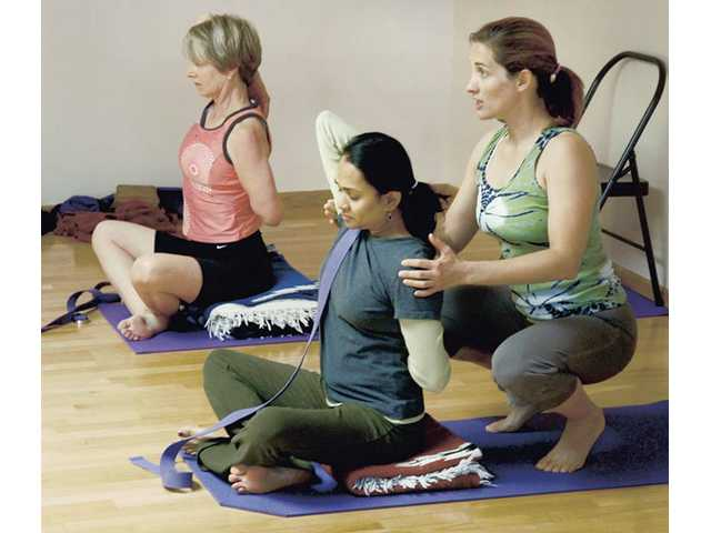 Martha Jones, left, and Parul Desai focus on releasing stress while Henigman guides them through the stretch.