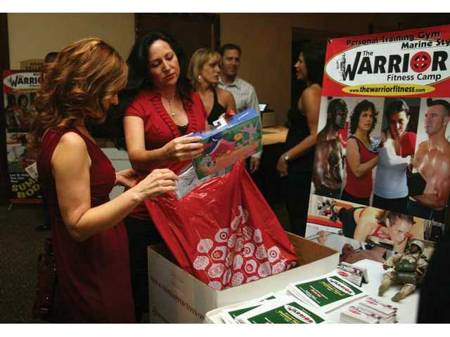 Joanne Aguayano and Cheryle Russell, both of Stevenson Ranch, drop off unwrapped toys for a Toys for Tots drive at Warrior Fitness Camp's holiday party Friday night at the Hyatt Valencia.
