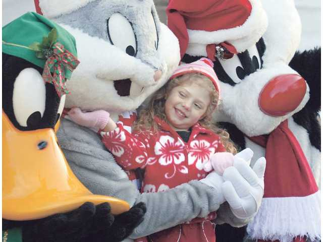 Dia Cameron, 3, of Valencia, poses for pictures with Looney Toon characters at the Henry Mayo Newhall Memorial Hospital Community Tree lighting celebration on Sunday which kicked off the holiday season. Hundreds gathered for the event, which is now in its 24th year.