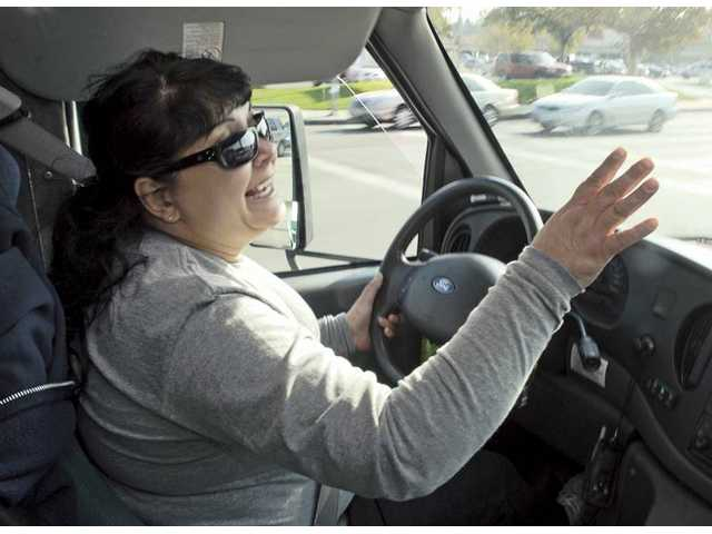 Driver Roxanne Brill waves as she spots a group of seniors waiting to be picked up at the 99 Cents Only Store on Lyons Ave in Newhall. Brill is one of five drivers who help senior living apartments with para-transit bus service.