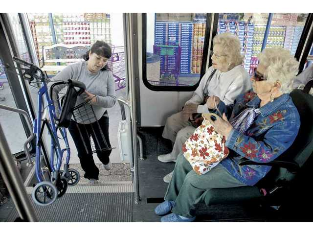 Brill, left, secures Karen Frisch's wheelchair for the bus ride to her doctor's appointment.