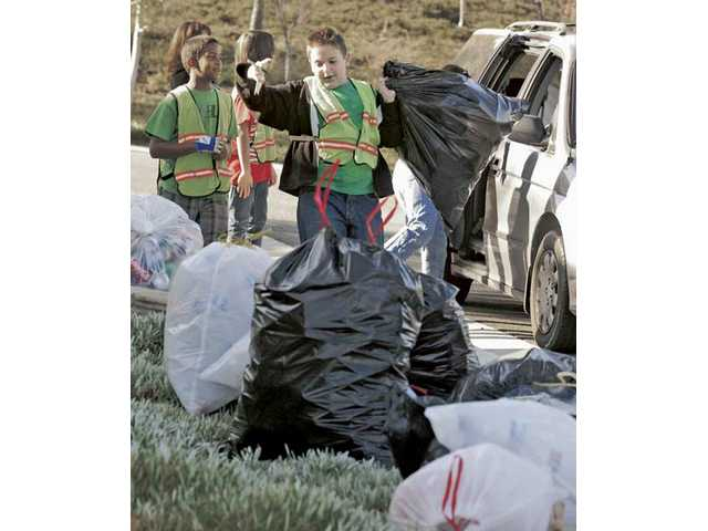 Sixth-graders Donovan Williams, left, and Tristin Kurtz cheer as they count the bags of recyclables collected at Fair Oaks Ranch Community School in Canyon Country during the school's second monthly recycling drive to raise funds for school projects.
