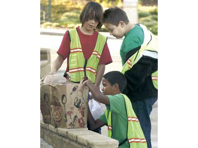 Kyle Anderson, left, and Tristin Kurtz, right, watch as Donovan Williams labels bags of recyclables by grade level.