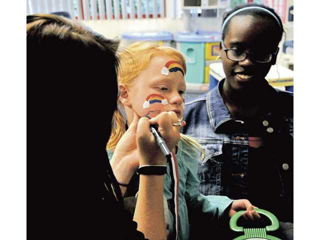 Anyah Anderson, 7, gets her face painted by students from the Saugus High School Choir during the Sport-A-Thon and Family Fun Day organized by the Santa Clarita Autism Asperger Network.