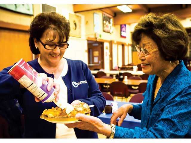 Marilyn Civita, branch service manager at the Stevenson Ranch Lockheed Federal Credit Union, left, puts whipped cream on a piece of apple pie for 82-year-old Ethel Kawata during lunch at the SCV Senior Center.