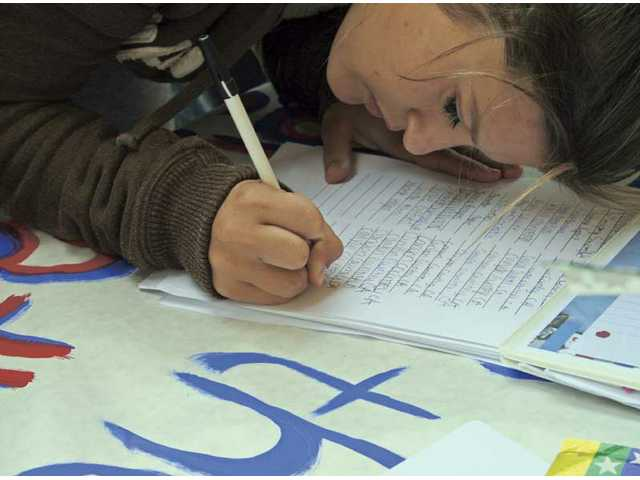 A Canyon High School student signs a petition during an event hosted by the Human Rights Watch Student Task Force chapters of Canyon and Valencia high schools.