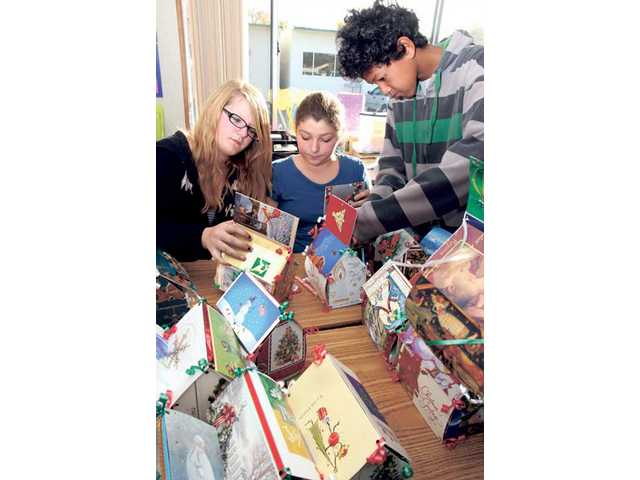 From left, Kelli Prince, Alison Gregg and Albert Goldson, members of the Sierra Vista Community Service (SiViCS) Club at Sierra Vista Junior High School arrange gift boxes made for local kids in need from recycled Christmas cards on Friday. The club's goal is to make 100 boxes and fill them with gifts and candy donated from other students at the school. The boxes will be delivered to the Santa Clarita Valley Food Pantry which will pass them out to families with young children.