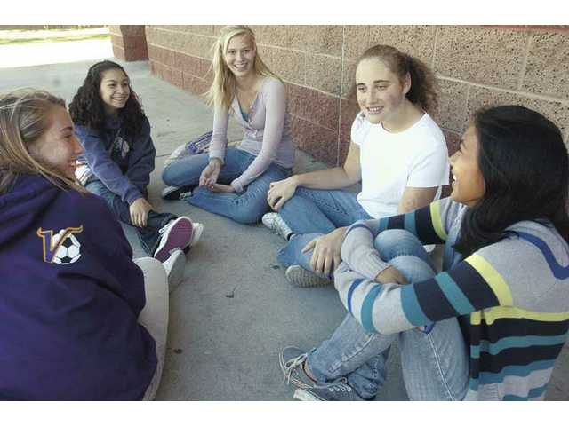Valencia High School Circle of Friends club sophomores, from left, Ada Rauch, Maribel Castillo, Hayley Lamson and Sarah Calor, right, sit with special needs student Lexi Grove, in white,  as they discuss music and fashion during lunch break at Valencia high on Friday.