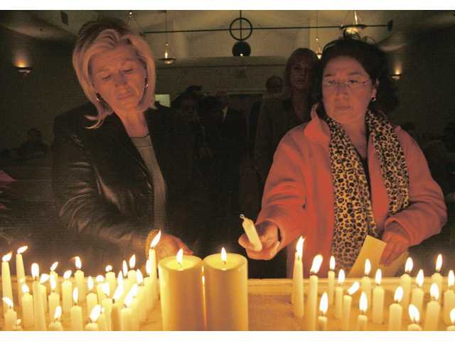 Gina Misitano, left, lights a candle for her son Royal Horton, as Stella Alonzo, lights one for her cousin's husband Jeff Cohen.