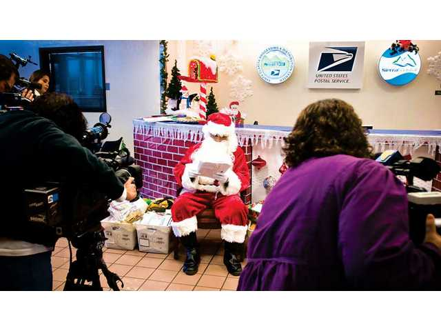 Santa Claus visited the Santa Clarita Valley Post Office Distribution Center Tuesday to read letters written by children to Santa.