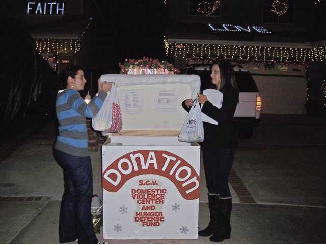 Signal Holiday Light Tour judges Tammy Marashlian, left, and Melissa Gasca make donations at Ash Court.