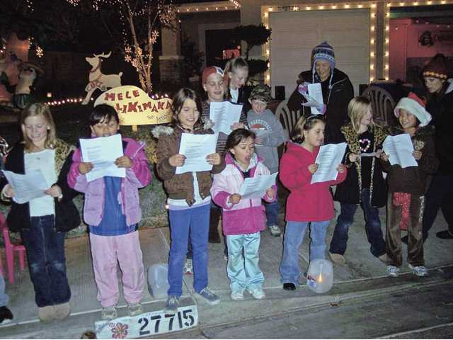 "Neighborhood children sing Christmas carols at Essex Place, defending Light Tour street champs which earned second place street honors on The Signal's 16th annual Holiday Light Tour. The street is known locally as ""Reindeer Road."" Visitors are encouraged to visit the ""photo spot"" and also to look for Rudolph."