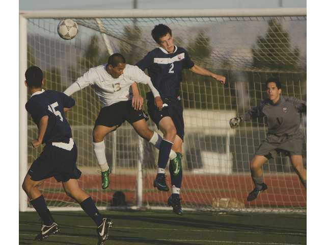 Grizzly Juan Trejo (13) is sandwiched between Chaminade's Michael Hajdu (15) and Ray Gylys as they all jump for the ball Thursday.