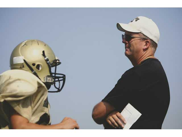 Steve Pinkston, right, coaches as a player runs by in 2007. Pinkston resigned Thursday after three years as head football coach at Golden Valley High.